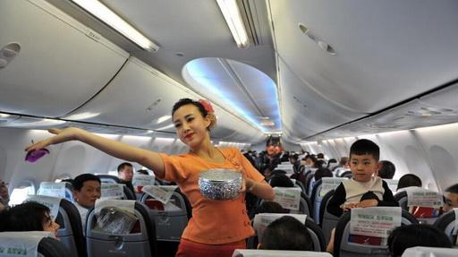 """飞机上过泼水节 空姐变身""""傣家少女""""向旅客送祝福"""